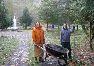 Thomas with Theravada monk clearing leaves from driveway during their Autumn visit