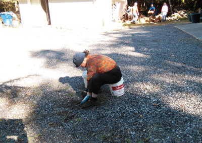 Kwo Long removing weeds from driveway